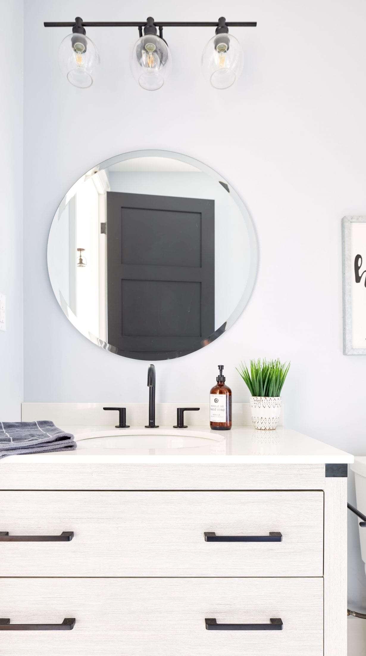 Guest bathroom round mirror above gray vanity