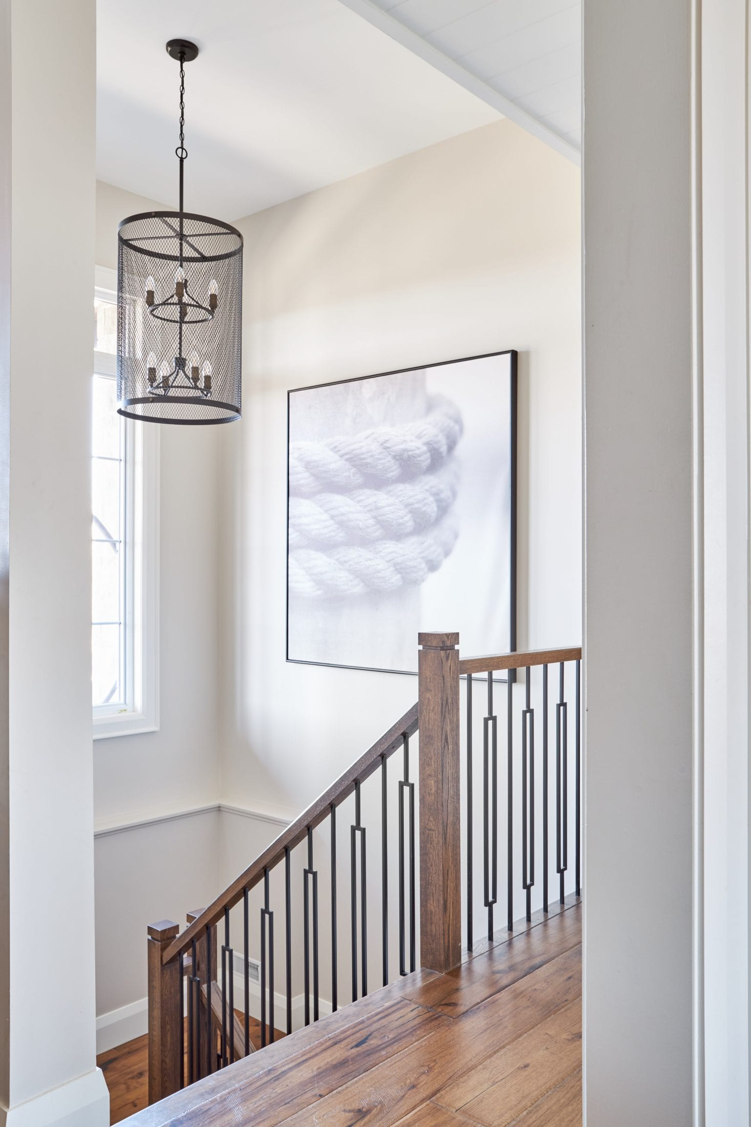 Staircase artwork ideas and large light fixture for tall stairwell